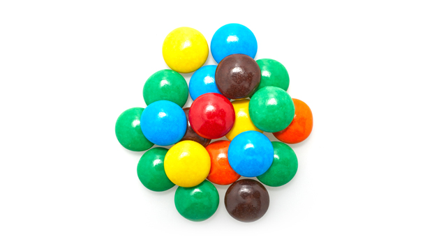 Sugar, hydrogenated vegetable oil, cocoa, whey, maltodexrin, soy lecithin (an emulsifier), natural waxes, titanium dioxide color, artificial flavors, artificial colors (yellow 5 lake, yellow 6 lake, red 40 lake, blue 1 lake, blue 2 lake), vanillin, BHA Y BHT (preservatives).